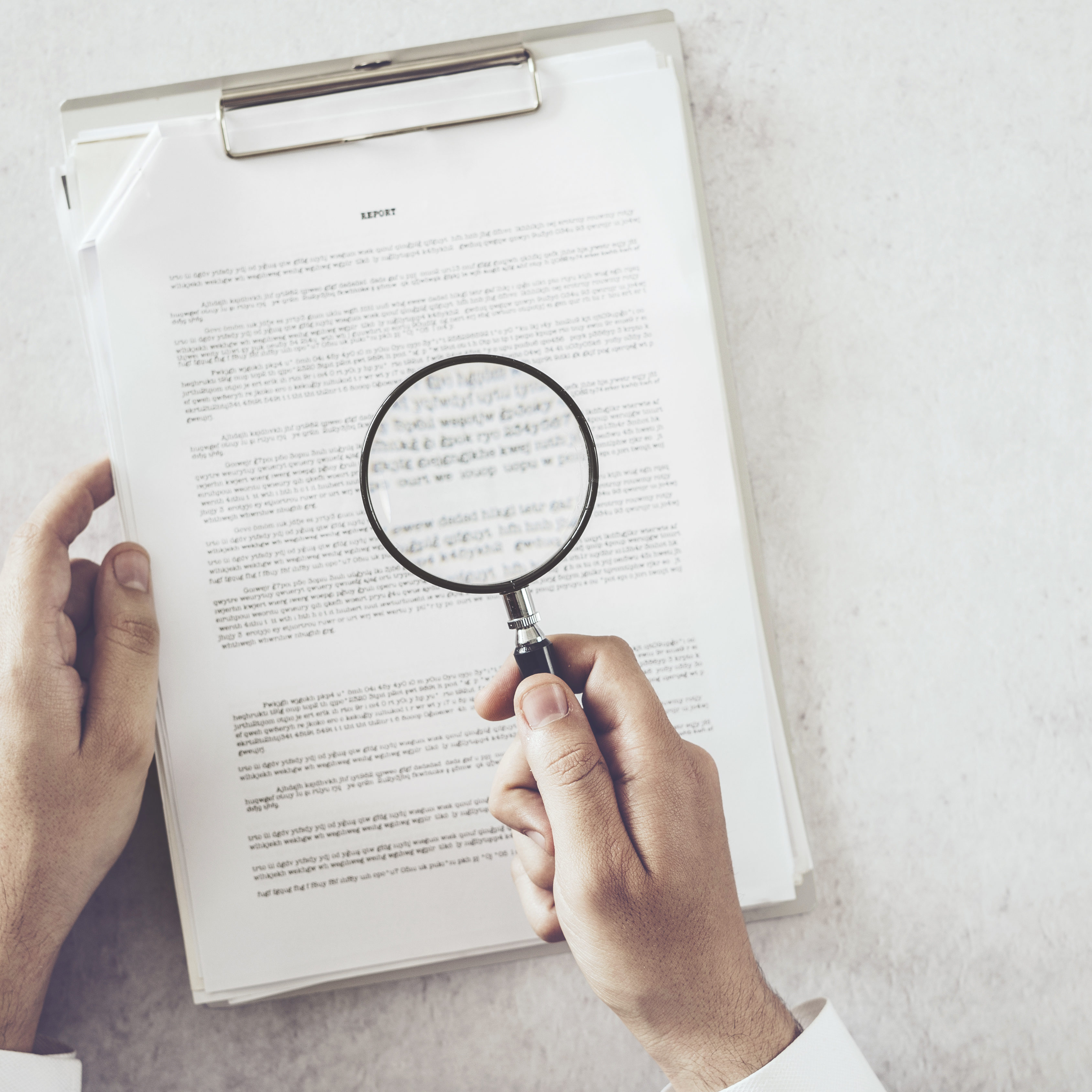 Man hands looking document with magnifying glass