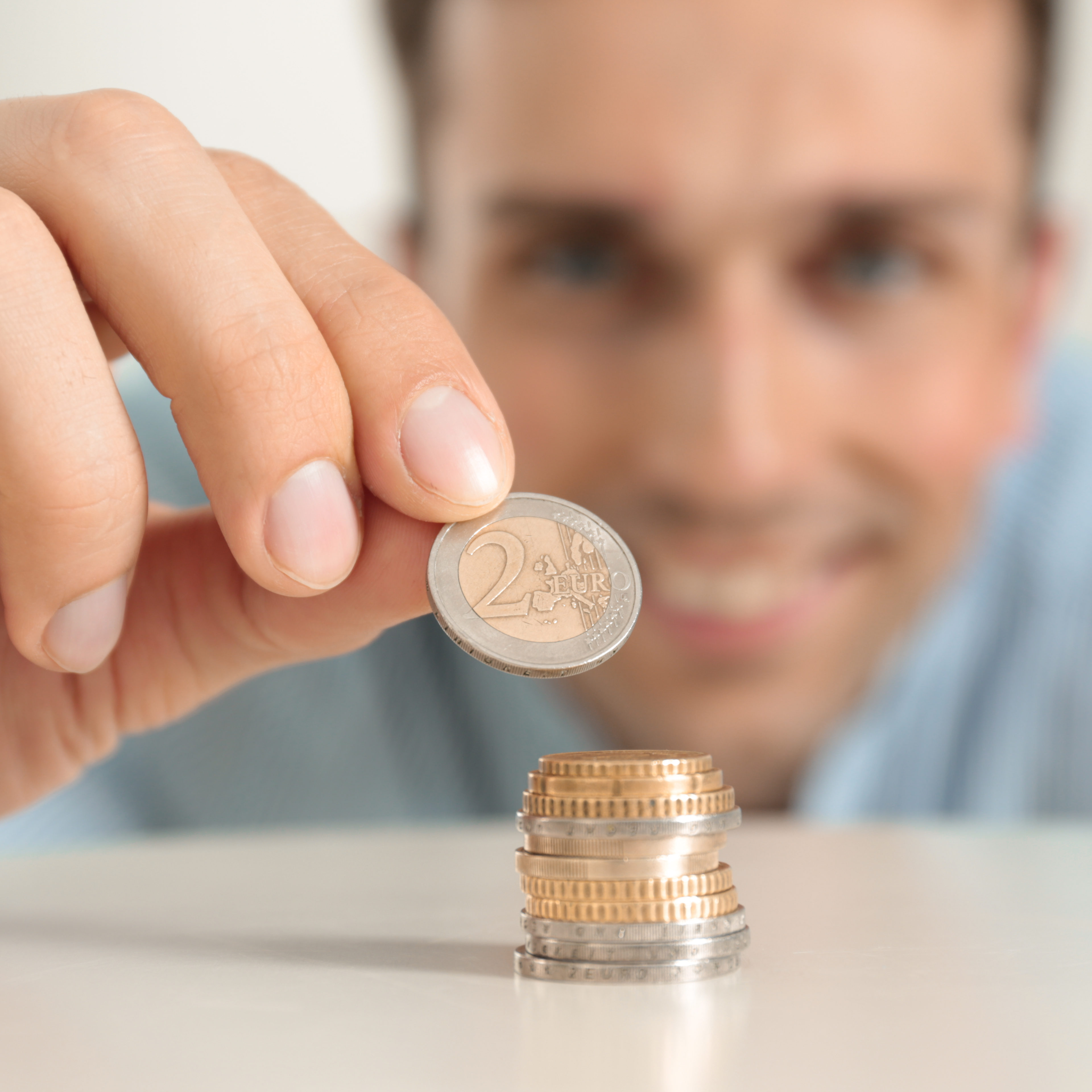 Young smiling man stacking coins at table, focus on hand